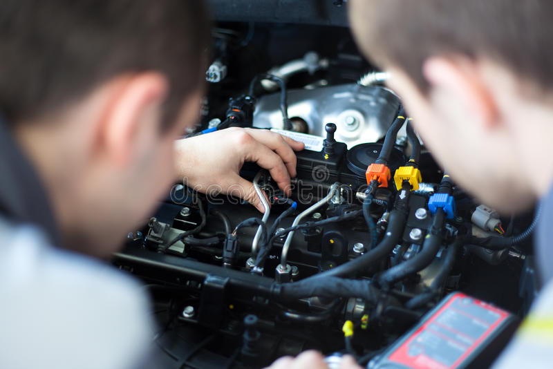 Mechanics at repair shop. two confident mechanics working on a car engine. Mechanics at repair shop. Top view of two confident mechanics working on a car engine stock photography