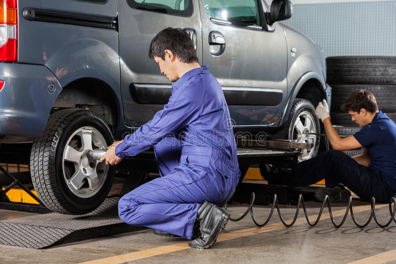 Mechanics Repairing Car Tires royalty free stock photography