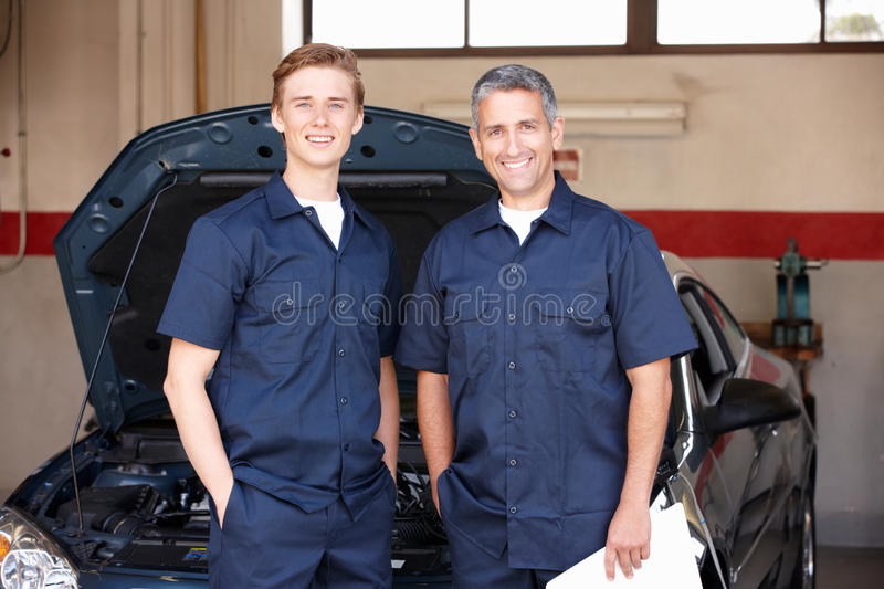 Mechanics standing in front of car. Mechanics at work standing in front of car smiling at camera royalty free stock image