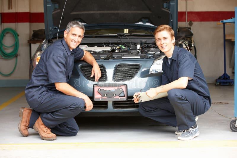 Mechanics working on car. Mechanics at work on car smiling at camera royalty free stock image