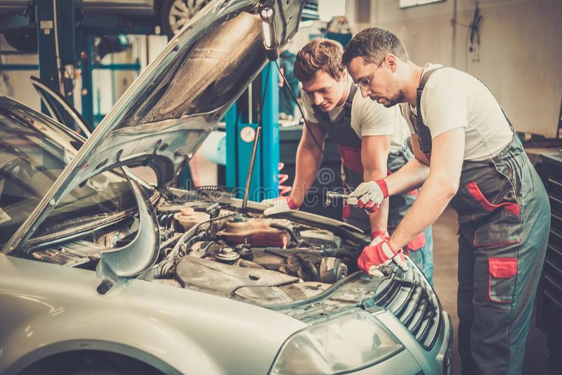 Mechanics in a workshop. Two mechanics fixing car in a workshop royalty free stock images