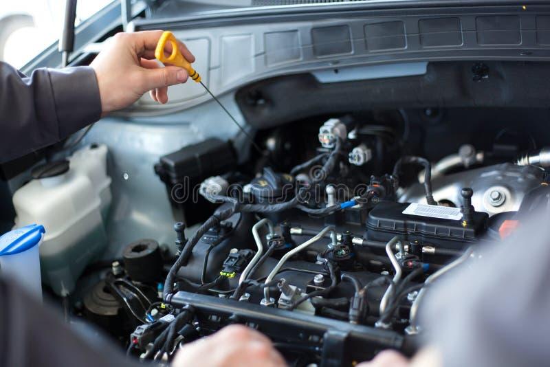 Mechanicy przy remontowym sklepem dwa mechanika pracuje na samochodowym silniku fotografia stock