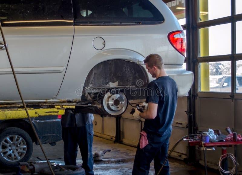 Mechanicy robi hamulcowej pracie na pojazdzie obrazy stock