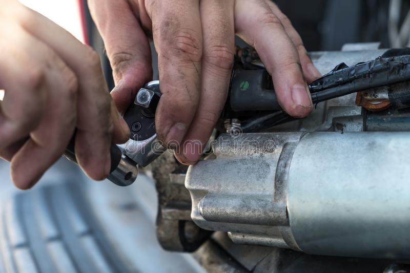 Mechanicy z brudnymi rękami naprawiają łamanego starteru na car/Automot zdjęcie royalty free