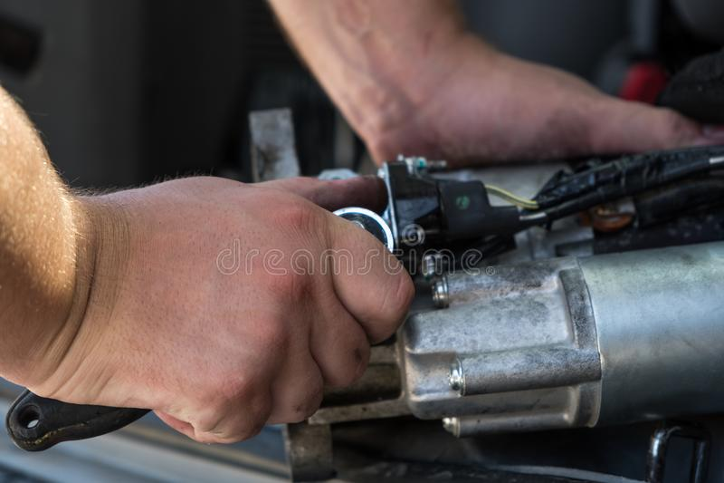 Mechanicy z brudnymi rękami naprawiają łamanego starteru na car/Automot obraz stock