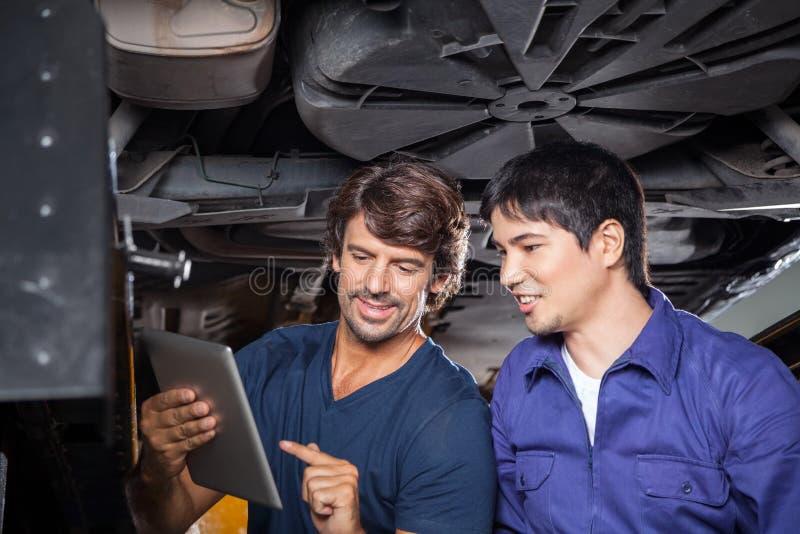 Mechanik Dyskutuje Nad Cyfrowej pastylką Z zdjęcie stock