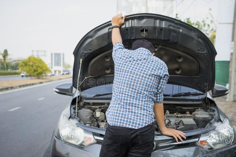 Mechanik jest ubranym rękawiczki otwiera samochodowego kapiszon sprawdza samochodowego parowozowego olej na drodze po samochodowe zdjęcie stock