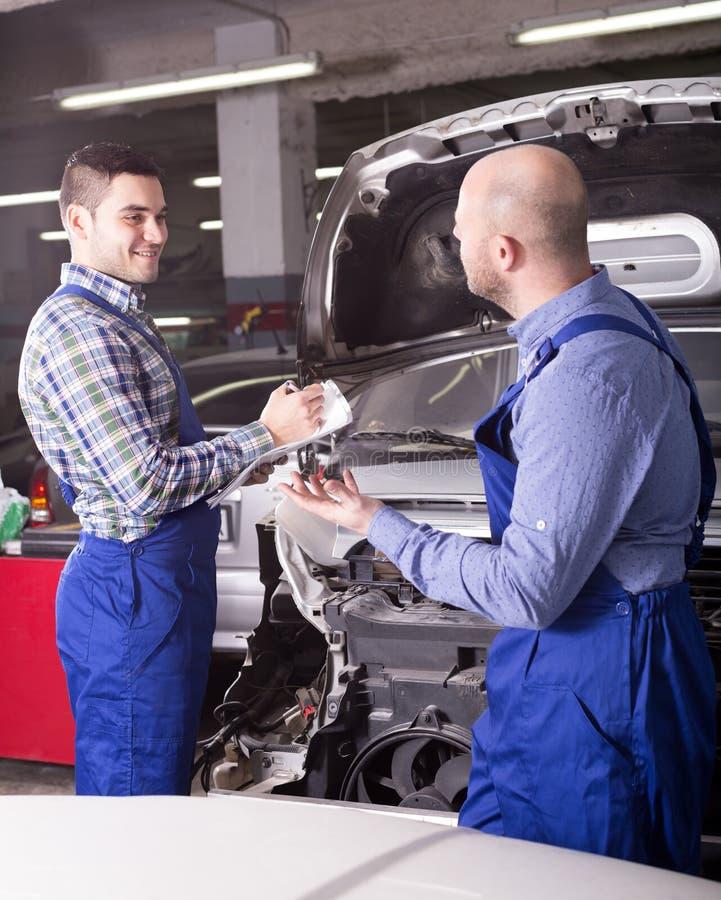 Mechanik kalkuluje cenę praca przy auto naprawą fotografia stock