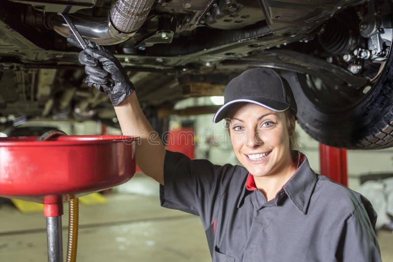 Mechanik kobieta pracuje na samochodzie w jego sklepie obraz stock