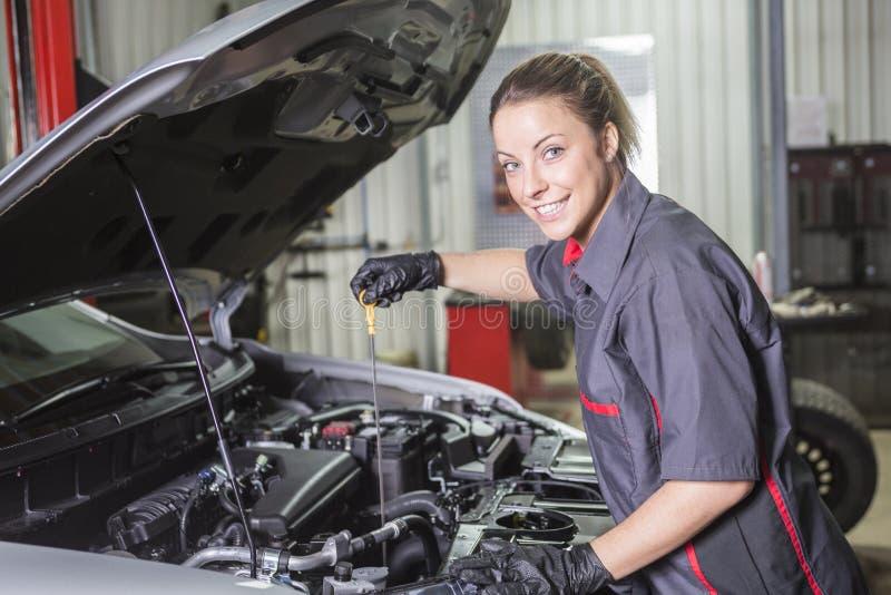 Mechanik kobieta pracuje na samochodzie w jego sklepie obrazy stock