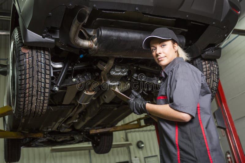 Mechanik kobieta pracuje na samochodzie w jego sklepie obrazy royalty free