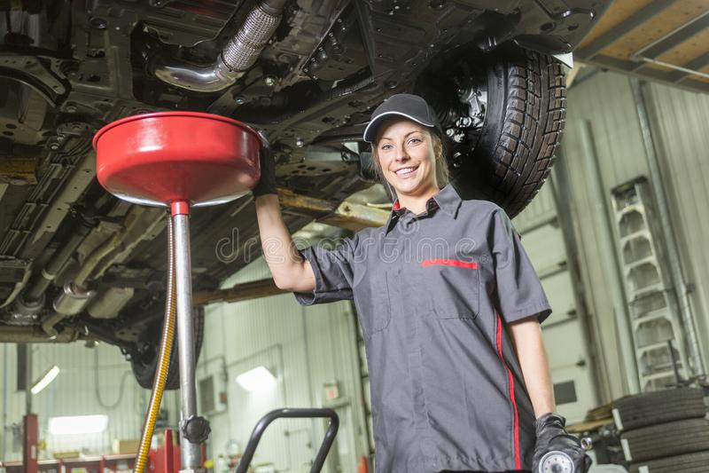 Mechanik kobieta pracuje na samochodzie w jego sklepie zdjęcie stock