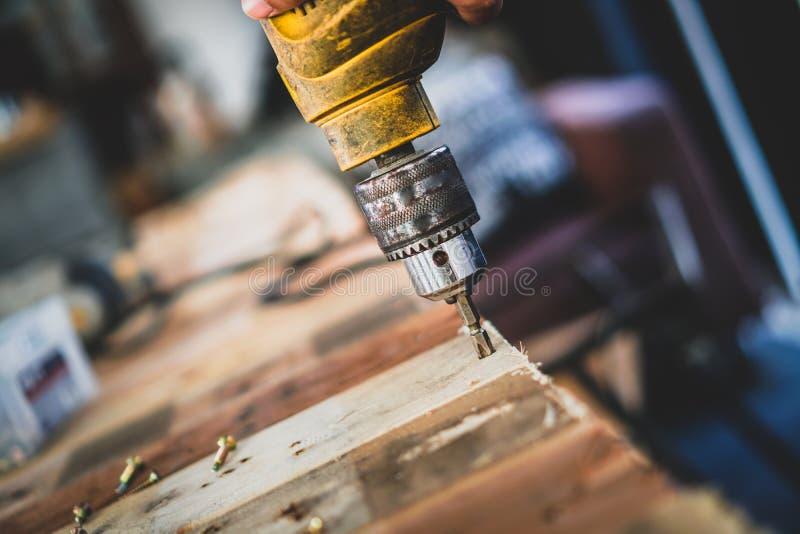 Mechanik mężczyzna, używa świder musztrować drewno fotografia stock