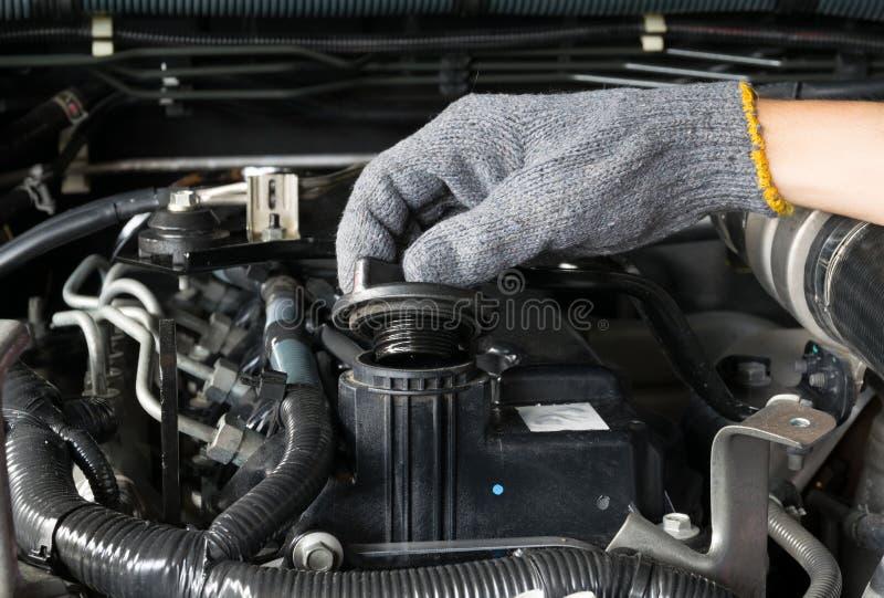 Mechanik otwiera nafcianą nakrętkę od samochodowego silnika obraz royalty free