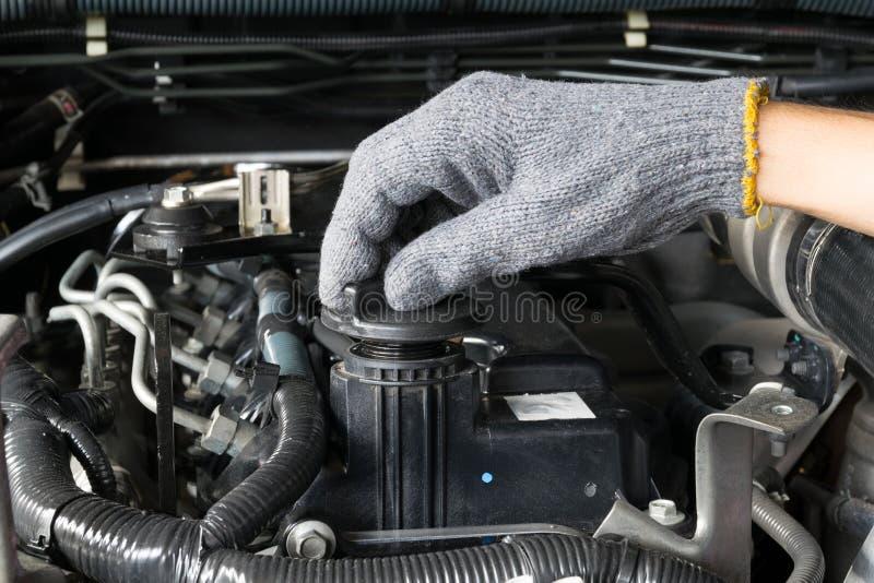 Mechanik otwiera nafcianą nakrętkę od samochodowego silnika fotografia royalty free