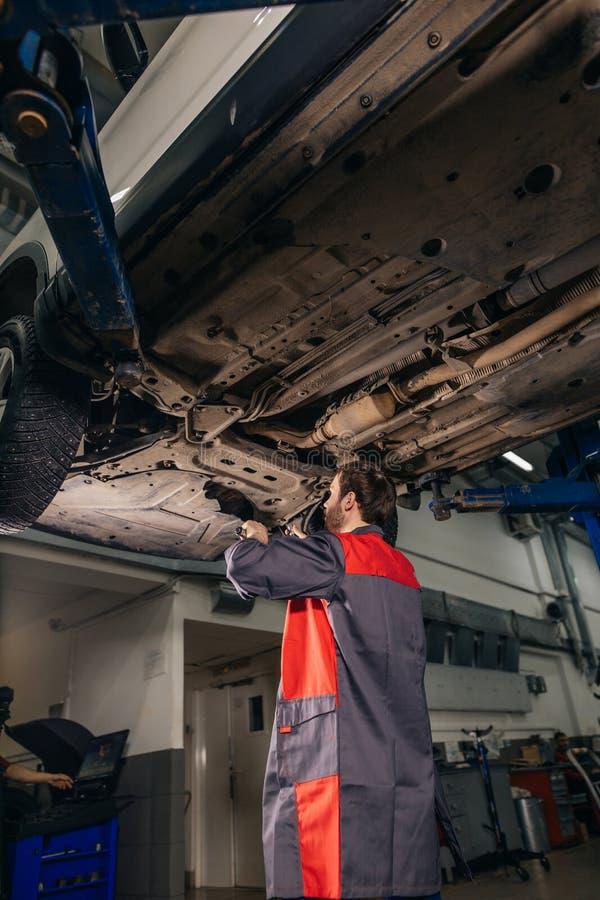 Mechanik pod samochodem w garaż examing oponie i technicznym warunku zdjęcie royalty free