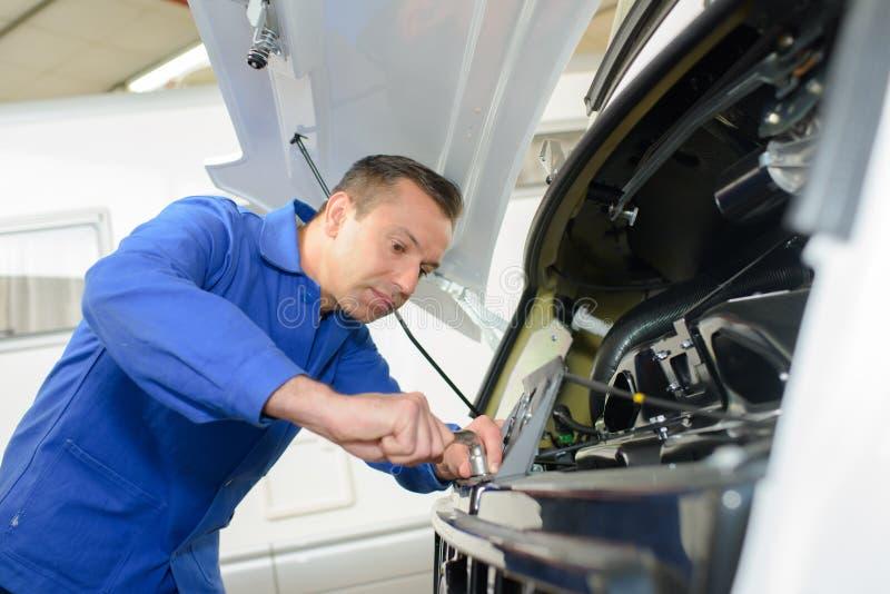Mechanik pracuje na przodu silnika karawanie fotografia stock