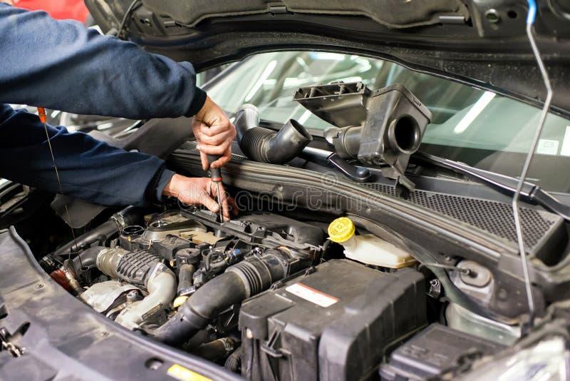Mechanik pracuje na samochodowym silniku robi naprawom obraz stock