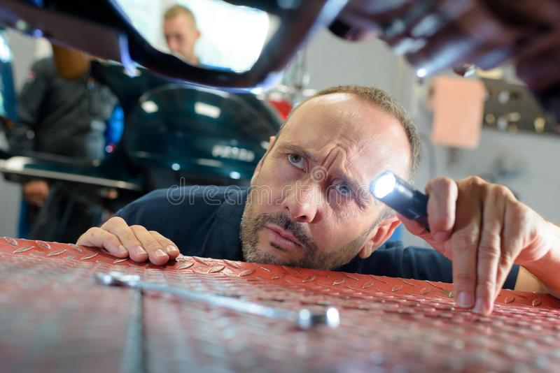 Mechanik pracuje na spodu samochodzie wynoszącym obraz royalty free