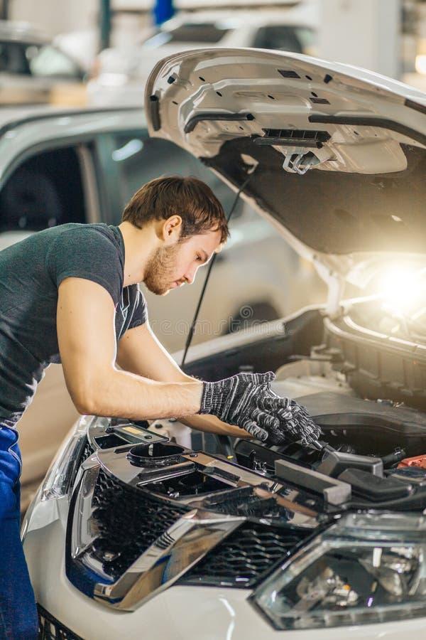 Mechanik pracuje pod samochodowym kapiszonem w remontowym garażu zdjęcie royalty free