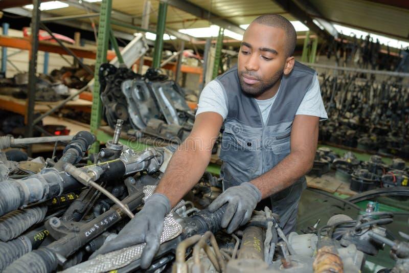 Mechanik przy sterta używać samochodu częściami obraz stock