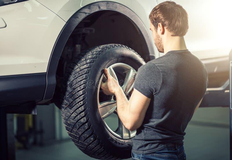 Mechanik przystosowywa opony koło przy remontowym garażem fotografia stock