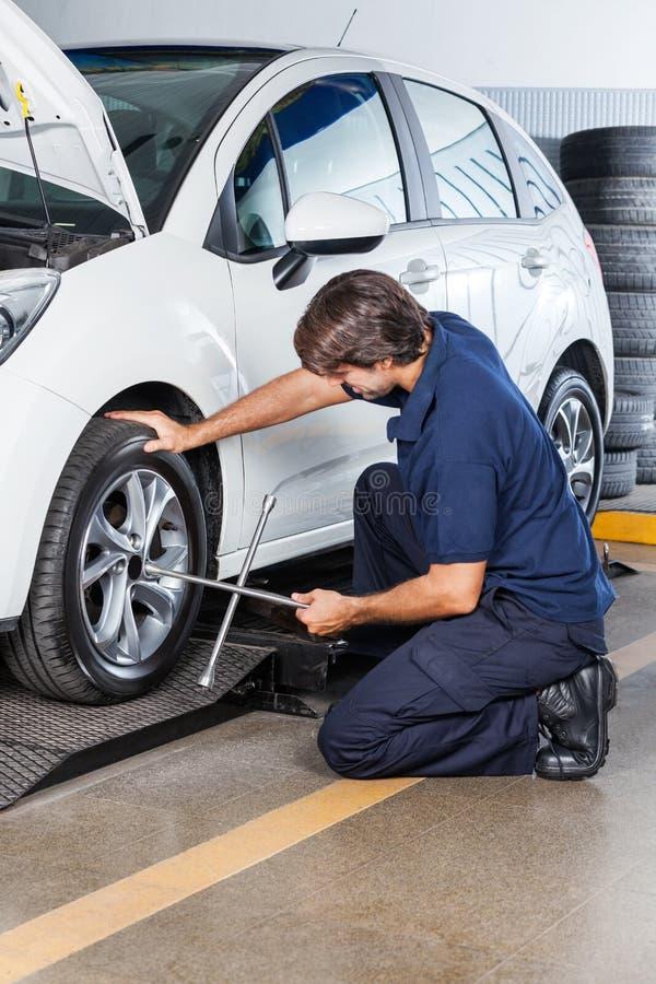 Mechanik Przystosowywa Samochodową oponę Z obręcza wyrwaniem Przy garażem obraz royalty free