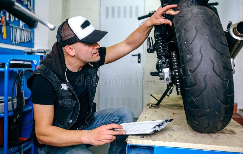 Mechanik sprawdza koło dostosowywający motocykl fotografia stock