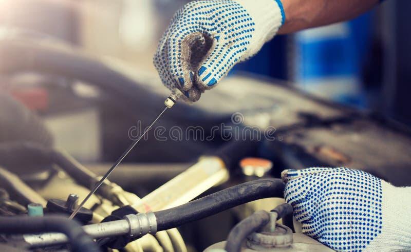Mechanik sprawdza motorowego nafcianego poziom z dipstick fotografia royalty free