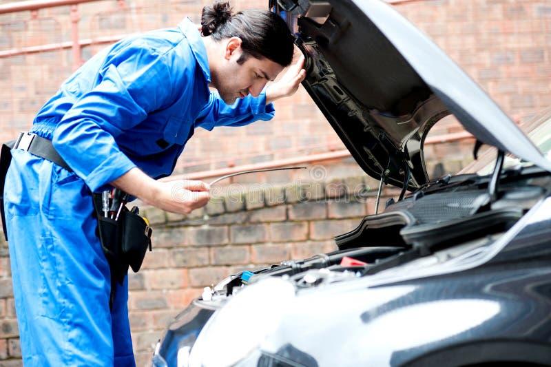 Mechanik sprawdza motorowego olej samochód obraz royalty free