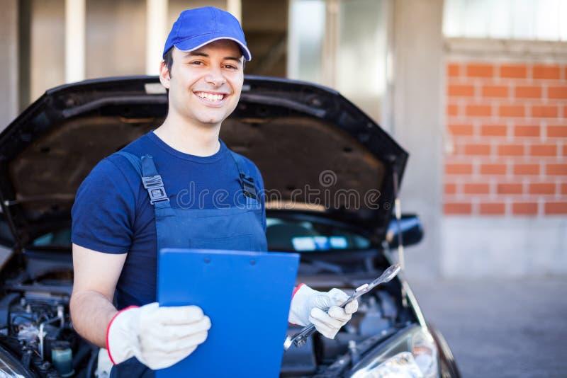 Mechanik trzyma schowek przed samochodem fotografia stock