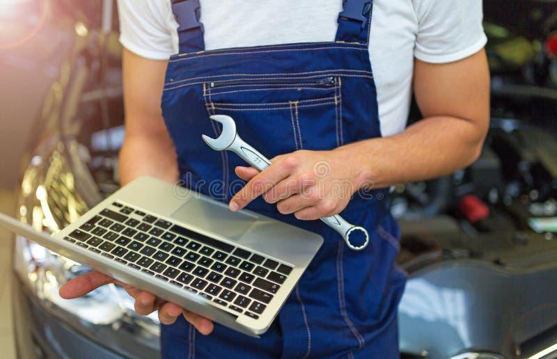 Mechanik Używa laptop Podczas gdy Egzamininujący Samochodowego silnika zdjęcie stock