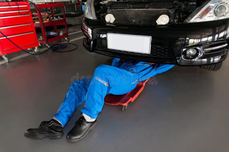 Mechanik w błękita munduru łgarskim puszku i działanie pod samochodem przy zdjęcie royalty free