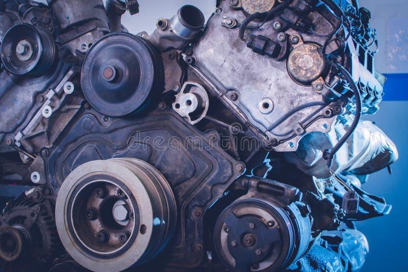 Mechanik w błękita munduru łgarskim puszku i działanie pod samochodem przy samochód usługa garażujemy obrazy royalty free