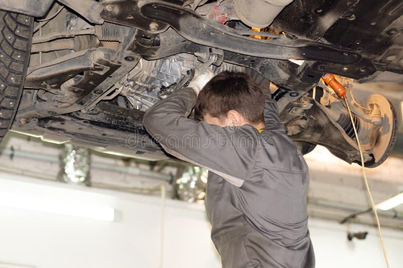 Mechanik w brudnym mundurze naprawia samochód fotografia royalty free