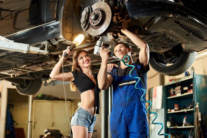 Mechanik z kobietą załatwia sterowniczego mechanizm samochód zdjęcie stock