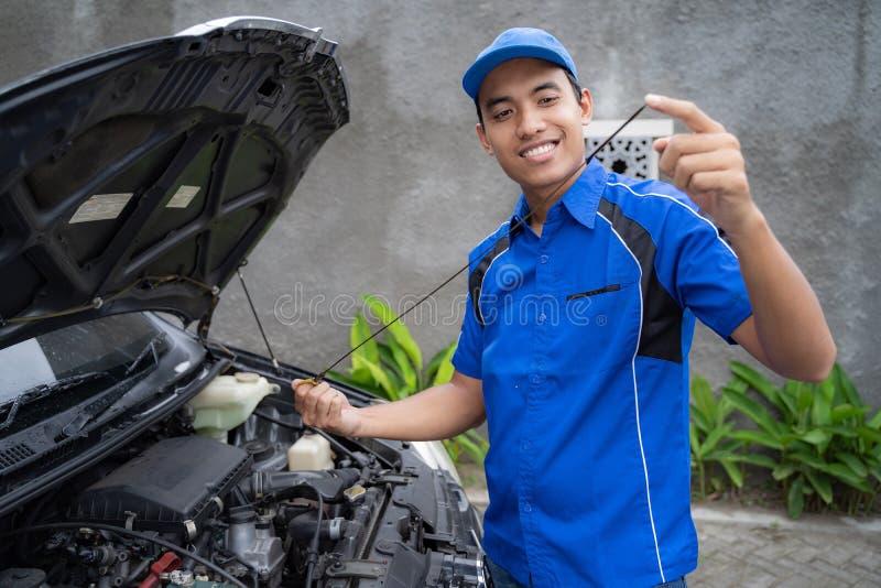 Mechanik z mundurem sprawdza samochodowego olej fotografia stock