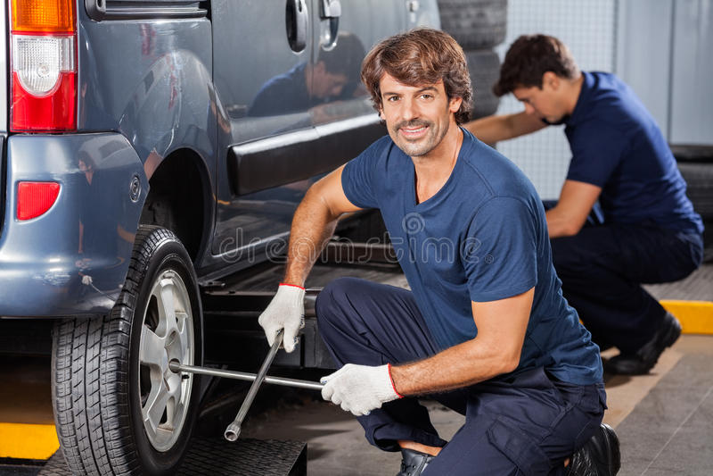 Mechanik Załatwia Samochodową oponę Przy Auto Remontowym sklepem fotografia royalty free