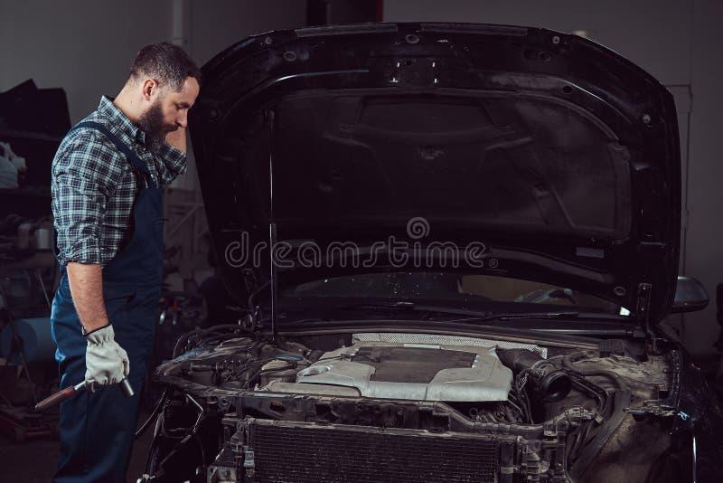Mechanika mężczyzna naprawia samochód w garażu w mundurze fotografia stock