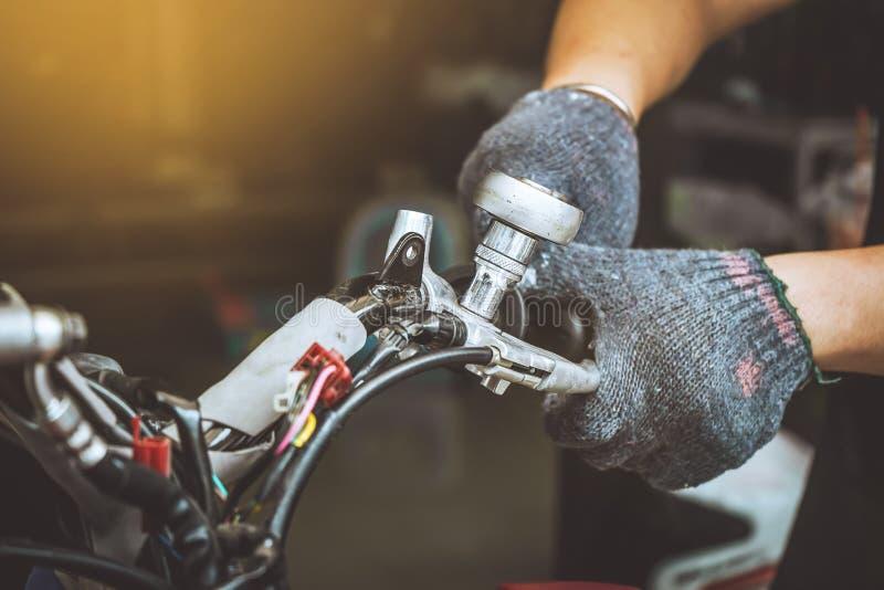 Mechanika mężczyzna używa wyrwanie Naprawiać motocykl lub utrzymywać przy zdjęcia royalty free