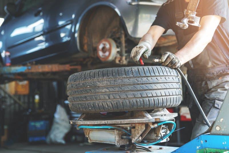 mechanika naprawiania opona przy samochodowym remontowym sklepem zdjęcia stock