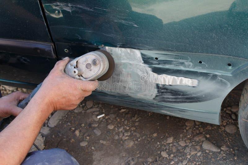 Mechanika pracownika repairman sanding polerowniczego samochodowego ciało i narządzanie samochód dla malować podczas naprawy zdjęcie stock