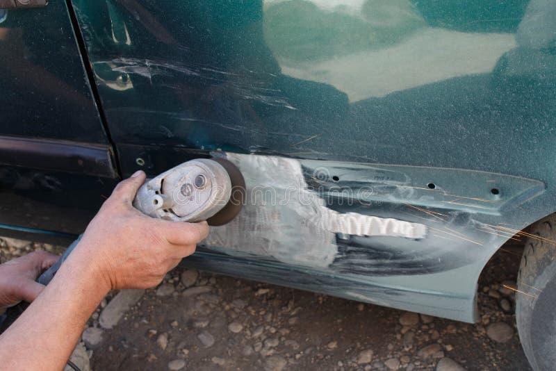 Mechanika pracownika repairman sanding polerowniczego samochodowego ciało i narządzanie samochód dla malować podczas naprawy fotografia stock