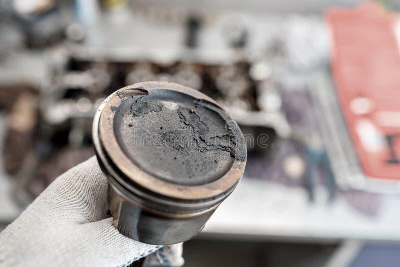 Mechanika repairman przy samochodu samochodowego silnika utrzymania naprawy pracą utrzymanie wewnątrz wręcza tłok z węgli depozyt obraz stock