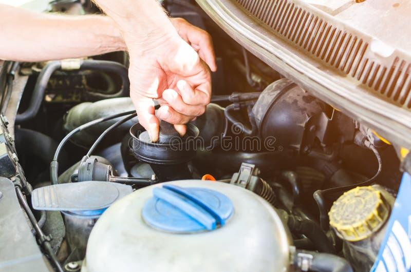 Mechanika ` s wręcza wykonywać samochodowego silnika czeka fotografia stock