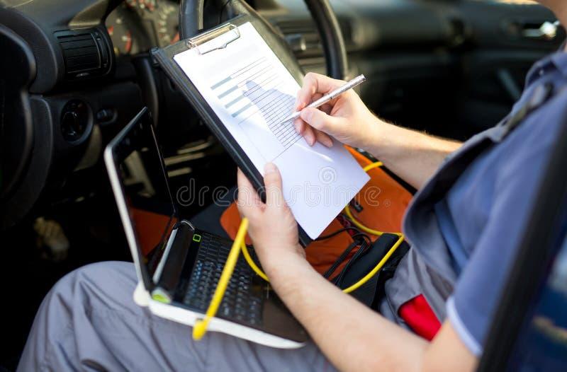 Mechanika writing na schowku, siedzi w samochodzie, zamyka up obrazy stock