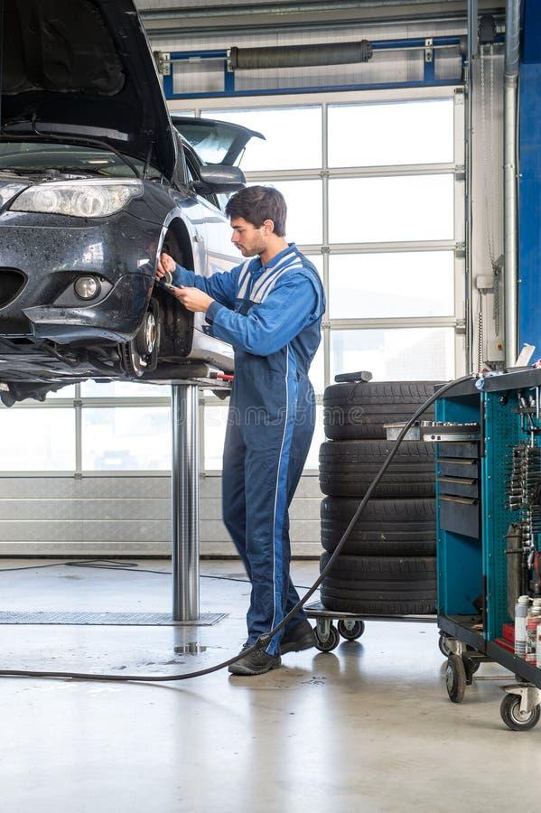 Mechaniker, arbeitend an einem Auto und überprüfen die Stärke der Bremse lizenzfreie stockbilder