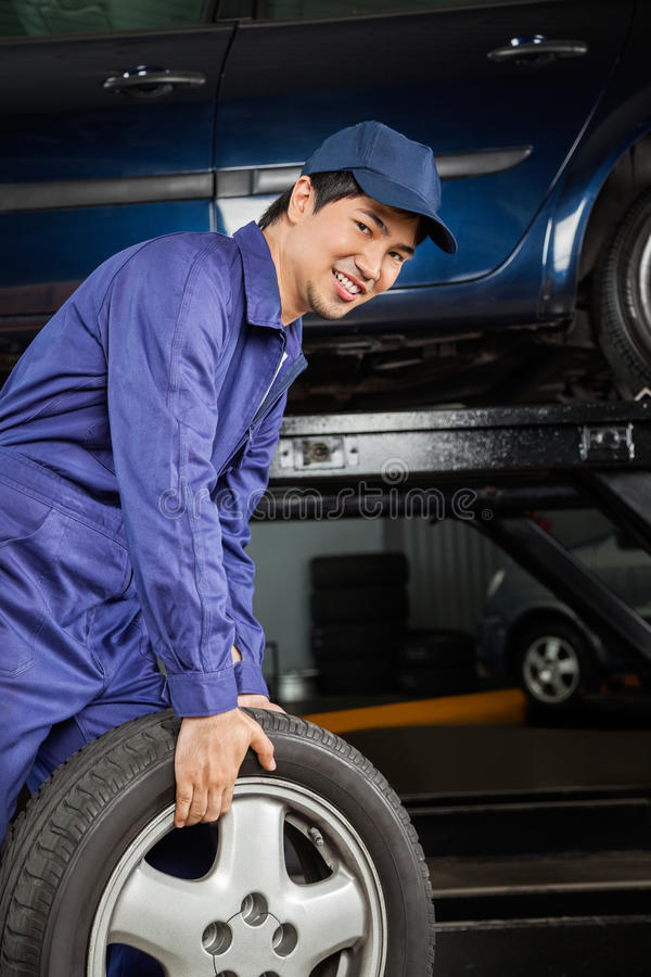 Mechaniker Carrying Car Tire an der Auto-Werkstatt lizenzfreie stockfotografie