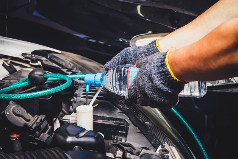 Mechaniker Check und Wasserwasser im Reservewasserbehälter für saubere Windschutzscheibe des Autos oben hinzufügen Service und Wa lizenzfreies stockfoto