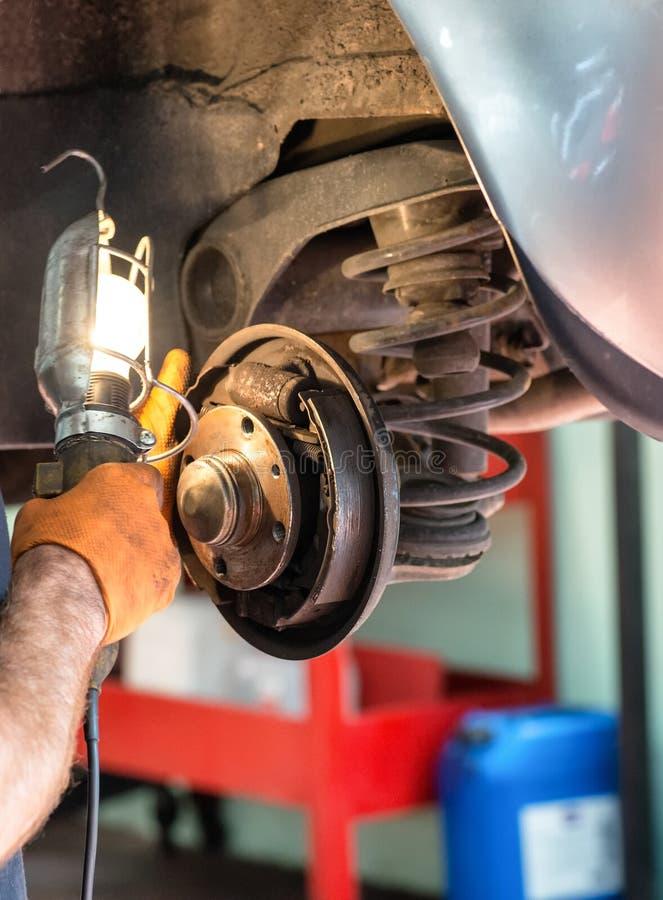 Mechaniker, der an Autobremsen arbeitet lizenzfreies stockfoto
